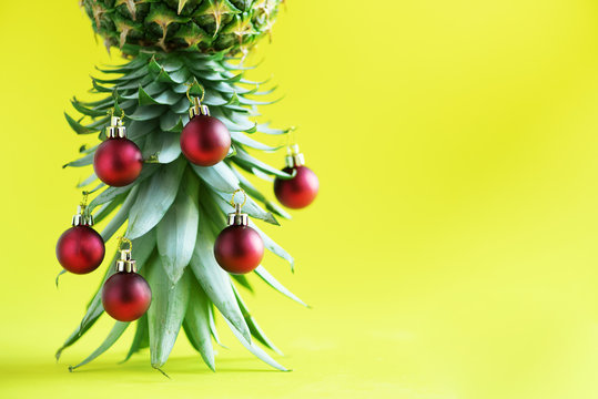 Creative Christmas tree made of pineapple and red bauble on yellow background, copy space. Greeting card, decoration for new year party. Holiday concept.