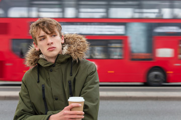 Foto op Aluminium Londen rode bus Male Young Adult Teen Drinking Coffee By Red London Bus