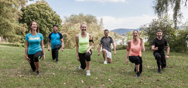 six sportive young people while training their legs muscles with lunges exercise. focus on blonde woman in the middle. healthy lifestyle sport concept