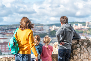 Family of four enjoying city view on a beautiful day. Back view of Father, mother and two children looking at panorama