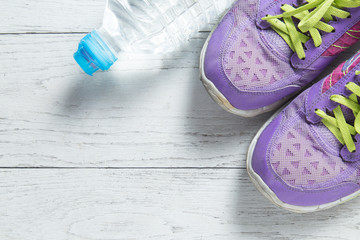 Sport flat lay purple shoes and water bottle on white wooden background with copyspace for your text. Concept healthy lifestyle and diet.