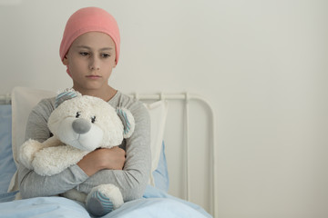 Sad girl with leukemia hugging plush toy in the hospital with copy space