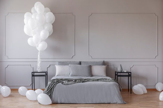 White balloons in spacious bedroom with king size bed with grey duvet and pillows between black bedside tables, real photo with copy space on the empty grey wall