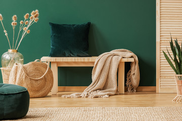 Emerald green pillow and beige blanket on wooden bench in stylish interior designed with natural materials, real photo with copy space on empty green wall