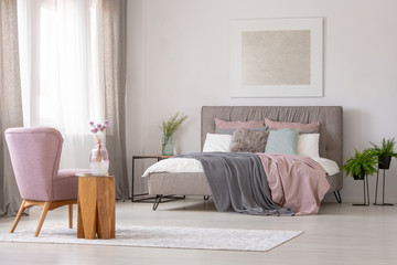 Flowers on wooden table next to pink armchair in grey bedroom interior with poster above bed. Real photo