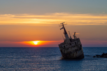 Picture ship wreck in the sea with sunset at the background