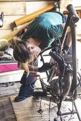 Female mechanic repairing motorbike in garage