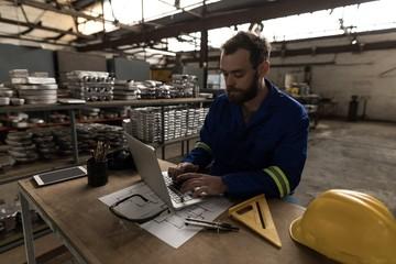 Blacksmith using laptop in workshop