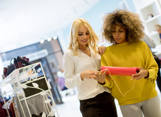 Two young multiethnic women buying purse in the store