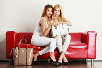 Two women sitting on sofa presenting bag
