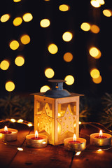 Christmas lantern with four candles and lights on a wooden board