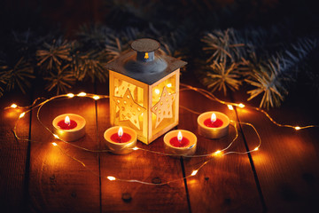 Top view of Christmas lantern with four candles on a wooden board