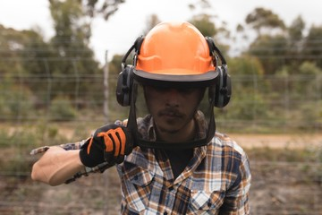 Lumberjack in hardhat at forest
