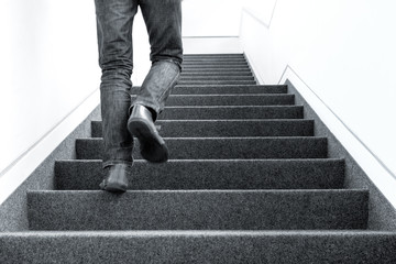 Black and white low angle picture of one man walking upstairs on staircase indoors