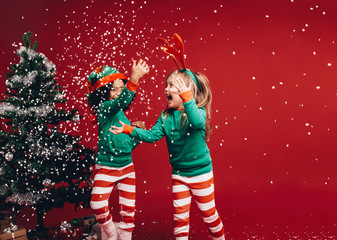 Little girls playing with the artificial snow flakes