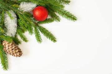 Christmas border of fir branches with a cone, a red ball and silvery leaves. Copy space.