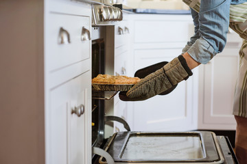 Woman taking pie out of the oven