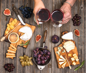 Top view of people having party, celebrating at wooden rustic table. Cheese plate served with wine, grapes, fig and honey. Hands holding wine glasses.