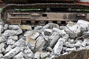 Heavy construction machine above pile of broken concrete at a building demolition site.