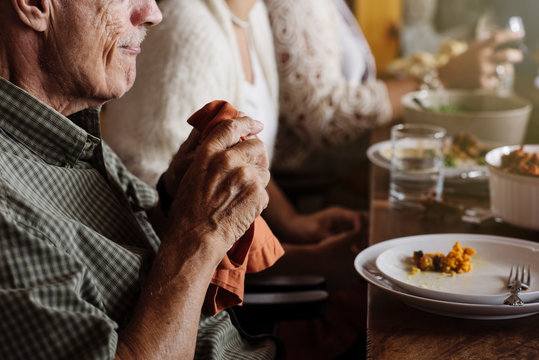 Senior man holding napkin at Thanksgiving dinner
