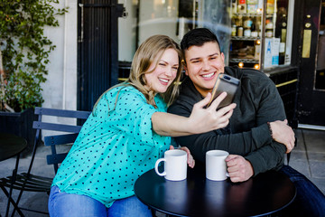 Smiling couple taking selfie with a cellphone at a sidewalk cafe