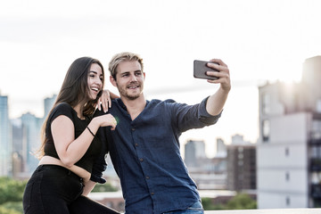 Couple taking selfie on a roof of a building