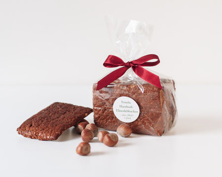 Traditional artisan glutenfree Nürnberger Elisenlebkuchen in foil packaging and red bow tie with sign saying 'finest Hazelnut Elisen Gingerbread' from Nuremberg, Franconia, Germany on white background