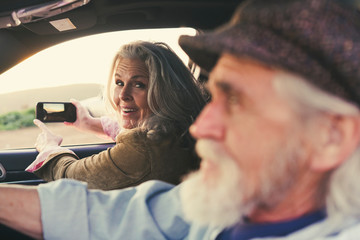 Woman taking pictures  while looking at man driving car