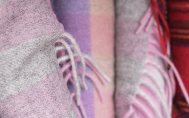 Close-up: warm gray-pink scarf is on a blur background of other woolen scarves. Preparing for winter. Warm clothes are a care of health.