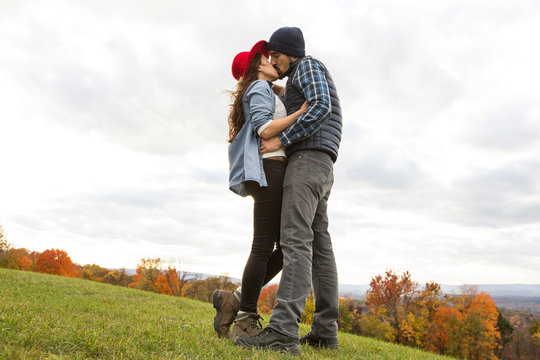 Couple kissing on a grassy field during autumn