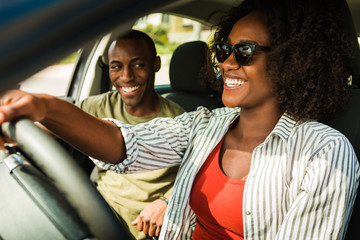 Smiling man looking at woman while she's driving a car