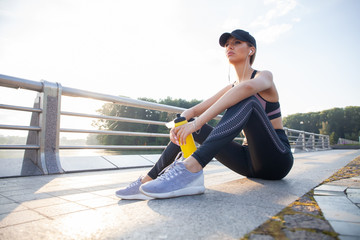 Portrait of tired fitness young woman outdoors in the city. Young woman runner resting after workout session on sunny morning.