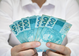 Close-up businessman wearing white shirt holding Brazilian money notes. Brazil one hundred (100) reais. Selective focus.