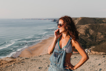 beautiful young woman on the top of a hill talking on her mobile phone and smiling. Summer time. Lifestyle