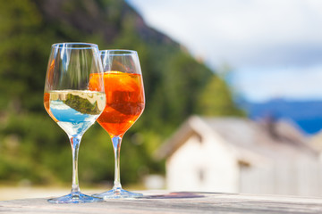 Chilled aperol spritz and prosesso glasses over mountains background