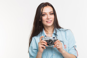 Photographer, hobby and people concept - Young brunette woman with retro camera on white background