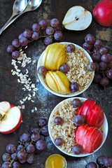 Oatmeal in bowls with apples, pears and grapes. Healthy breakfast with oatmeal and fruit.