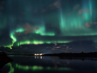 Strong, vivid, green and blue northern lights dancing over the water