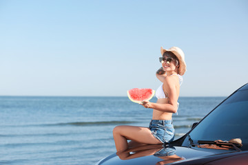Young woman with watermelon slice near car on beach. Space for text