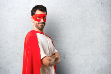 Superhero man with mask and red cape keeping the arms crossed in lateral position while smiling. Confident expression on textured grey background