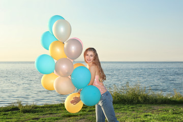 Beautiful young woman holding colorful balloons on riverside