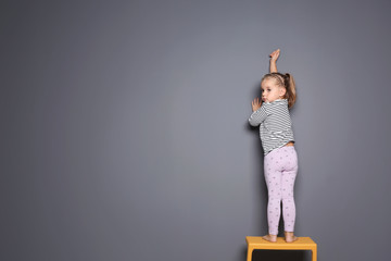 Little child drawing with colorful chalk on gray background. Space for design