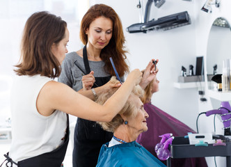Two hairdressers making hairstyle for elderly female
