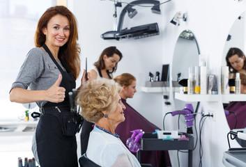 Hairdresser doing styling of senior woman