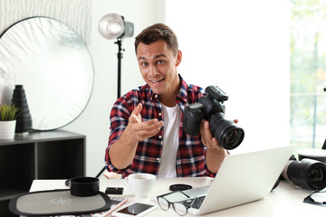 Portrait of photo blogger with camera and laptop at home. Online broadcast
