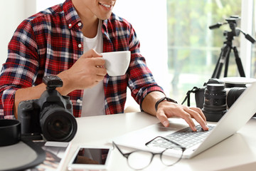 Photo blogger with laptop and cup of coffee at table indoors, closeup. Online broadcast