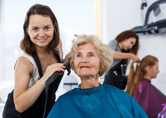 Hairdresser curling hair of elderly female