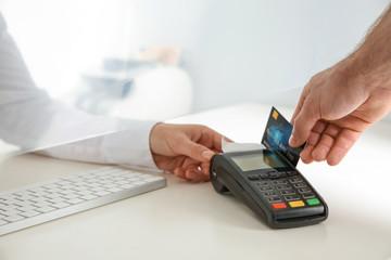 Man using bank terminal for credit card payment at cash department window, closeup