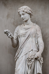 Poster Historic monument Ancient statue of sensual Greek renaissance era woman with a flower, Potsdam, Germany, details, closeup