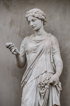 Ancient statue of sensual Greek renaissance era woman with a flower, Potsdam, Germany, details, closeup
